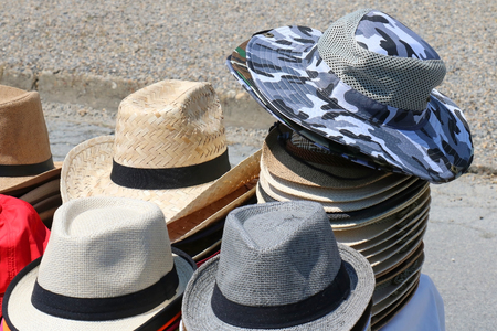 Heap of male summer hats sold on street market