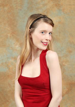 Joven mujer rubia con piel clara en vestido rojo con lápiz labial rojo