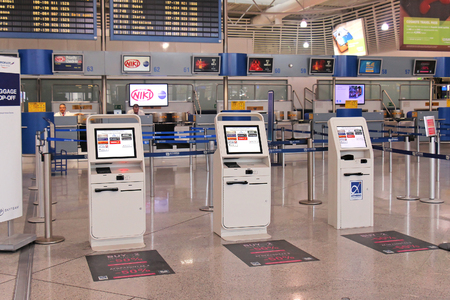 Athens, Greece - May 05, 2015: Self-service check in kiosks at Athens International Airport Eleftherios Venizelos with regular check in and baggage drop off counters staff behind.