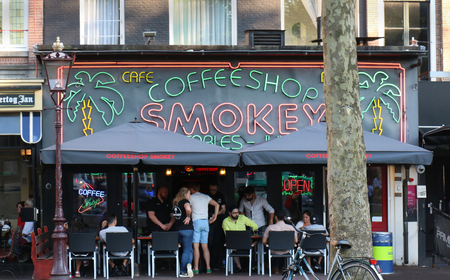AMSTERDAM, NETHERLANDS - MAY 14, 2018: People relaxing in front of Smokey coffeeshop in Amsterdam where the sale of cannabis for personal consumption in small quantities is allowed by licensed coffeeshops and is tolerated by the local authorities in Nethe 報道画像
