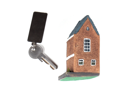 Small house model with key next to it on white background Stock Photo