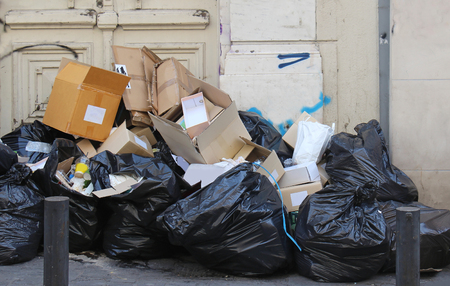 Large pile of garbage in black plastic bags and out of it on street pavement