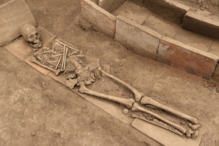Human skeleton next to an open tomb on dirty sand