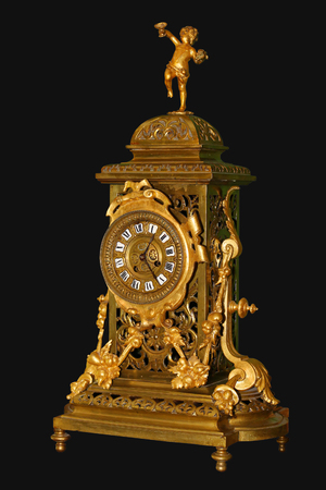 Antique gold fireplace clock with Roman numerals on black background