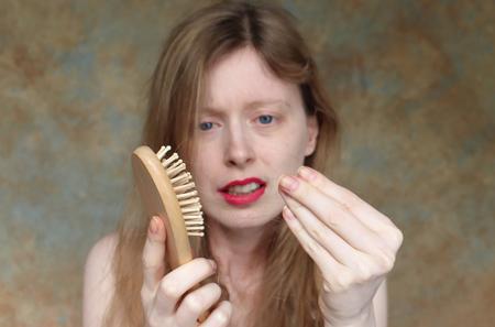 빗질하는 동안 빠진 머리카락을 보고 속상한 젊은 여성 스톡 콘텐츠