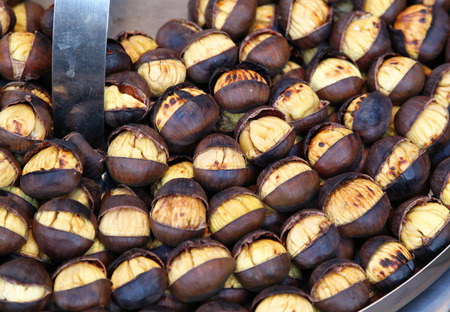 Large organic roasted chestnuts sold as street food Imagens