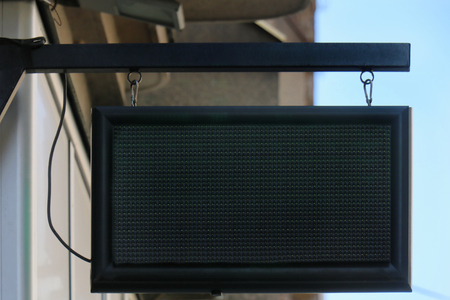 Empty led display for commercial hanging from building on street Imagens