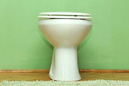 Closed modern toilet bowl with green wall in background