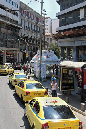 Athens, Greece - May 05, 2015: Busy street traffic in central Athens with row of taxis driving by and lots of people walking on the pavement and waiting near bus stop on warm sunny day. Editorial