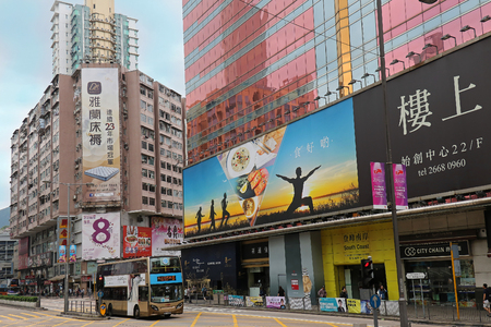 Hong Kong, China - April 28, 2017: Modern building architecture with lots of open shops in Nartan Road inside Hong Kong city centre. Public transport buses are on the street and many people are walking on pavement in front of shops. Editorial