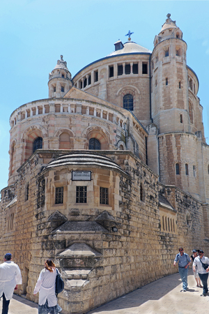 Mount Zion, Israel - May 24, 2018: Tourists and locals walking next to exterior walls of Dormition Abbey church outside the walls of the Old City near the Zion Gate in Jerusalem. It is also known as Basilica of Hagia Sion that stood on this spot during th