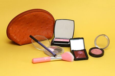 Set of beauty pink make up eye shadows and blush with orange case on yellow background Standard-Bild