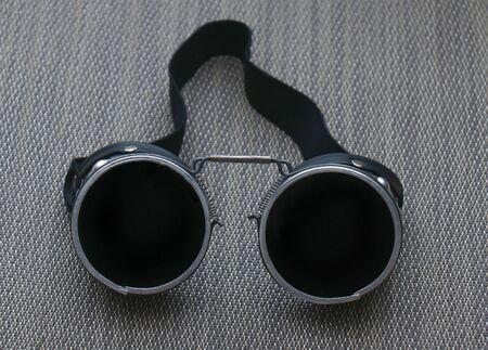 Schweißerschutzbrille mit dunkelschwarzen Gläsern auf ebener Fläche