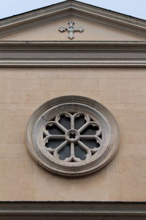 Circle window with stone decoration on church facade