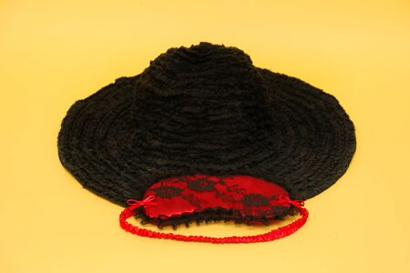Retro black textile hat with red sexy eye mask on yellow background Stok Fotoğraf