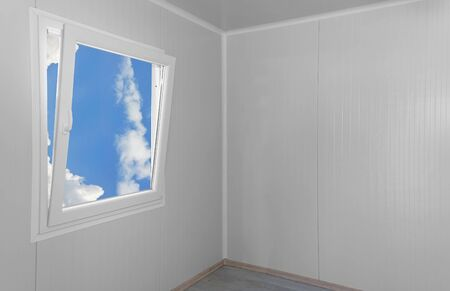 Empty modern interior room with open window shot from inside with view of sky and clouds