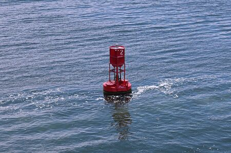 Floating red buoy in the river showing navigation and directions Stok Fotoğraf
