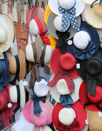 Colorful summer straw hats with ribbons and bows sold on market