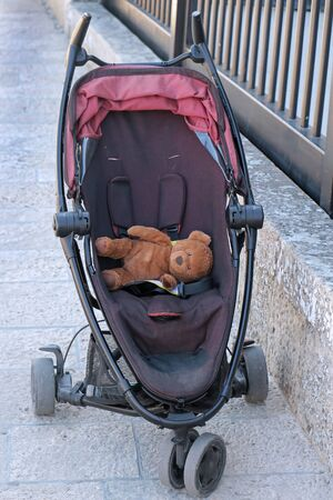 Empty baby stroller with teddy bear toy inside