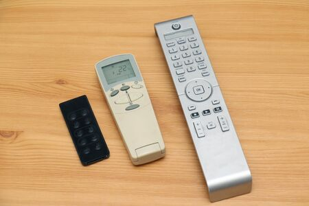 Remote controls for house appliances on wooden table