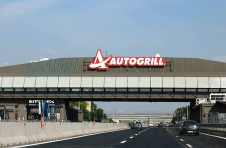 Milan, Italy - June 15, 2019: Highway on the way to Milan with cars on both sides of freeway and Autogrill restaurant with logo across on overlay bridge.