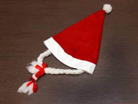 Female Santa Claus red hat on wooden background Stock Photo