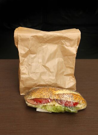Healthy sandwich with tomato and lettuce inside bun next to paper bag