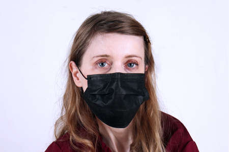 Pale complexion goth style young teenage girl wearing black disposable mask for virus protection