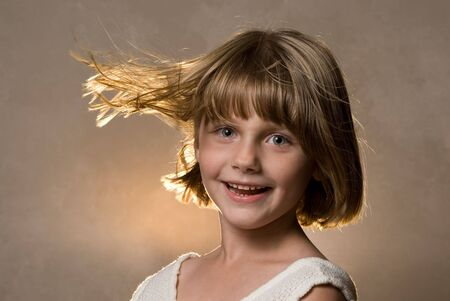 Girl smiles with backlight on wind blown hair Stock Photo - 4090363