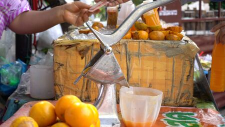 Orange juice shop with juicer and Orange juice squeezing into bottles. On the table there is Thai text meaning fresh.