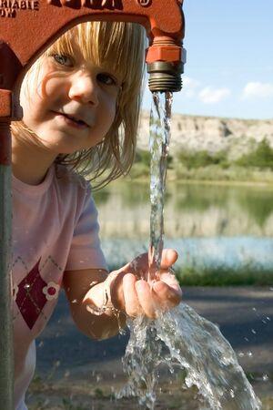 bomba de agua: Peque�a muchacha que juega en bomba de agua