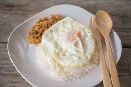 cooked rice: chicken fried garlic and egg fried with cooked rice on wood table