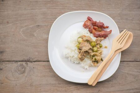 cooked rice: green curry pork and fried pork with cooked rice on wood table