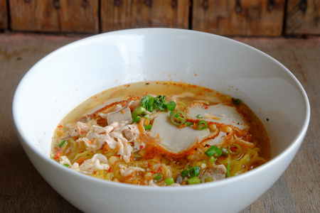 spicy tom yum noodle with pork on wood floor