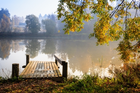 Autumn landscape with mist on the lake and a pier bathing on sunshine