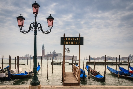 Gondolas in lagoon of Venice with a church on the background photo