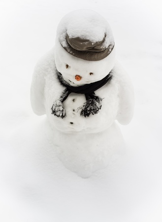 uneasy: Upset looking snowman melting on hot spring weather Stock Photo