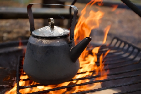 Coffee pan over the campfire with fire and flames