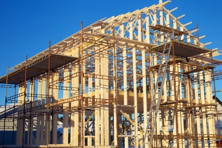 Residential construction site with incomplete home framing and scaffolds Stock Photo