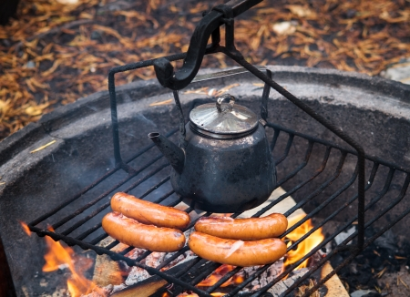 coffee pot: Coffee pan and sausages over the campfire with fire and flames Stock Photo