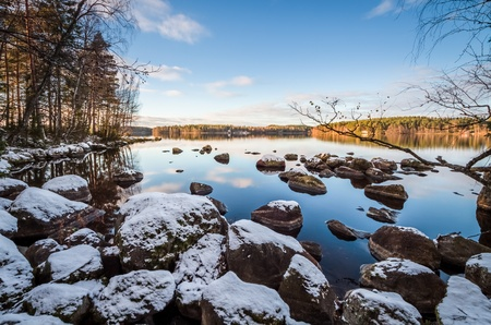 First snow on the rocks with stunning lake scene in Finland photo