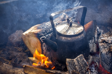 Making coffee in the Fireplace when hiking in the nature is the most relaxing activity you can do Stock Photo - 23285965