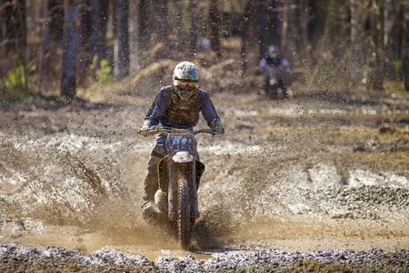 Motocross driver on wet and muddy terrain in Finland  photo