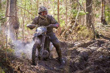 Motocross driver stuck in the mud on wet and muddy terrain  photo