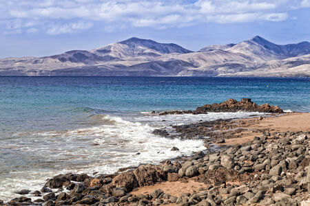 Arid landscape in the sea shore in Lanzarote with volcanoes on the background Stock Photo - 28505632