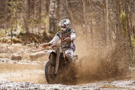 Motocross racer on wet and muddy terrain in Parola, Finland. Stock Photo
