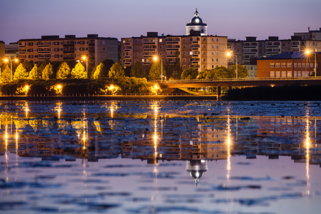 nightscene: Nightscene of Hämeenlinna in Finland  City lights reflecting on the lake and church tower reaching to the sky