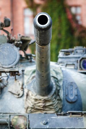 tanque de guerra: Tanque de guerra torreta de cerca. Un ca��n de un tanque militar se�al� al cielo. Antiguo cuartel construcci�n en el fondo. Foto de archivo