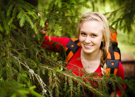 people and nature: Young blonde woman hiking and hiding in the forest.