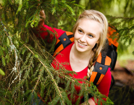 Young blonde woman hiking and hiding under a tree in the forest.